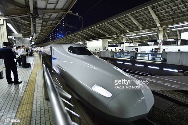 A bullet train is seen parked as passengers wait for operations to resume at a train station in Tokyo following an earthquake on May 30 2015 A...