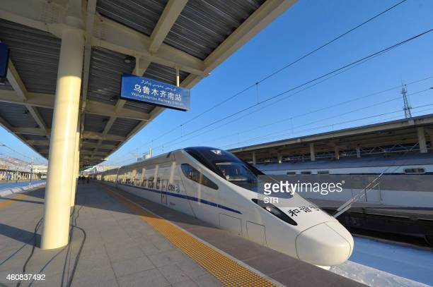 A bullet train stops at the platform before it travels to Lanzhou from the Urumqi south railway station in Urumqi northwest China's Xinjiang region...