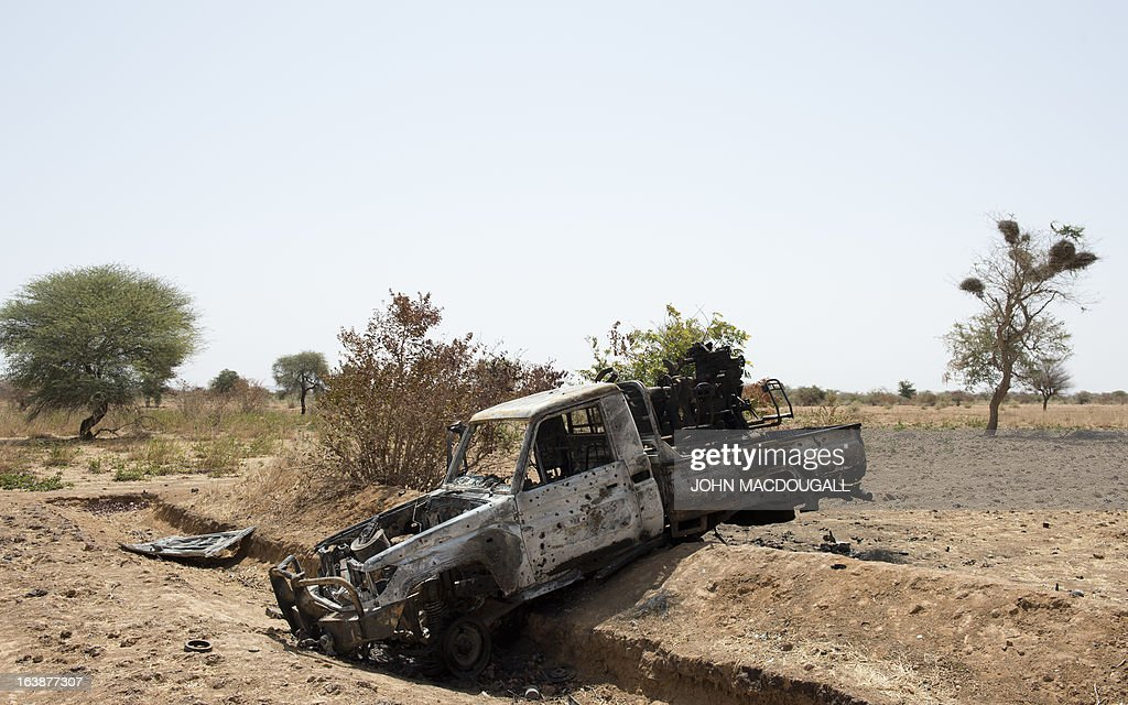 A bullet-ridden pickup truck belonging to Islamic extremists lies in a ditch off the road outside the central Malian town of Kona on March 8, 2013.