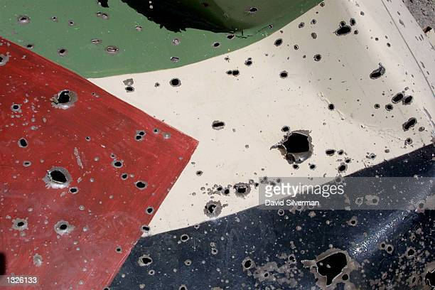 A bulletriddled metal Palestinian flag which a day before adorned a Palestinian police post lies abandoned in the street July 13 2001 in the West...