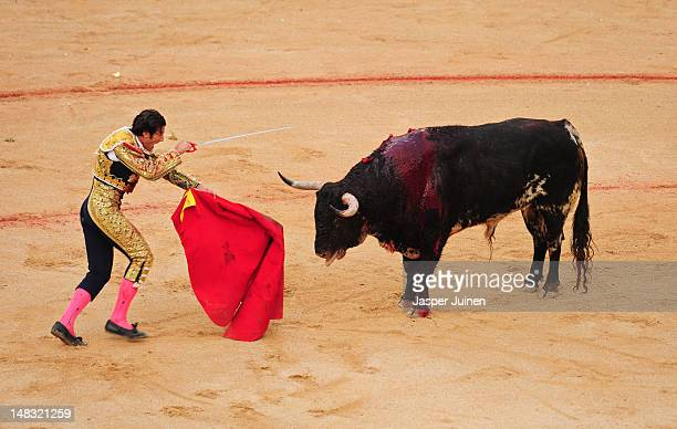 Bullfighter aims his sword at an El Pilar fighting bull to kill it on the fourth day of the San Fermin runningofthebulls on July 10 2012 in Pamplona...