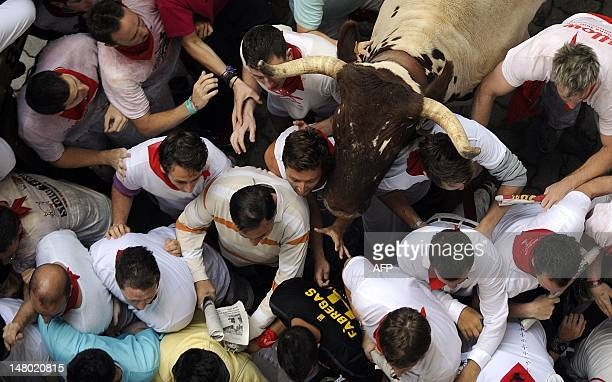 A bullock runs in front of the crowd packed at the entrance of the bullring during the second run of the bulls of the San Fermin festival on July 8...