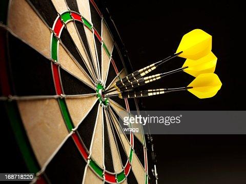 Bulls Eye in a Dartboard with Yellow Darts
