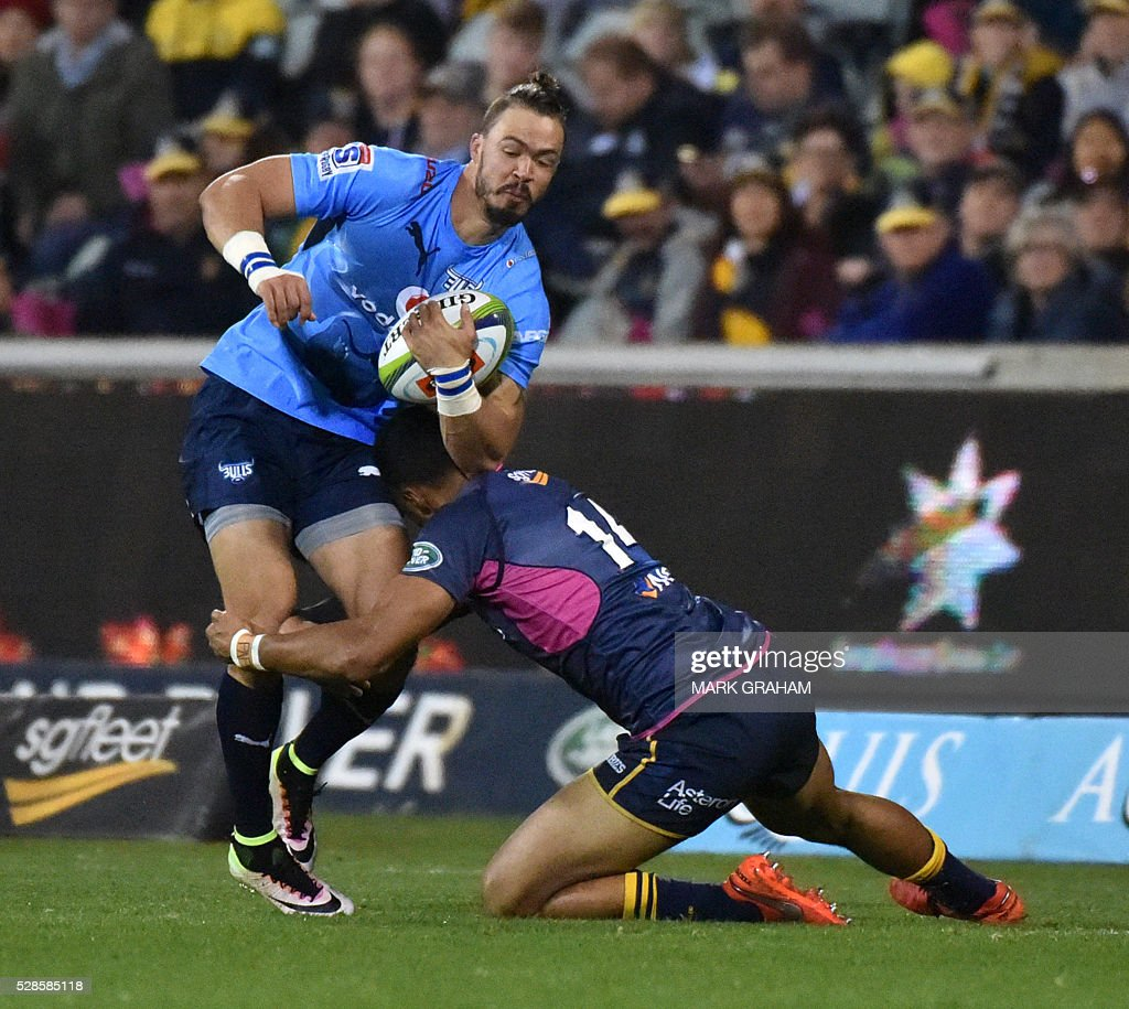 Bulls player Alberic Basson (L) is tackled by Brumbies player Nigel Ah Wong (R) during / AFP / MARK