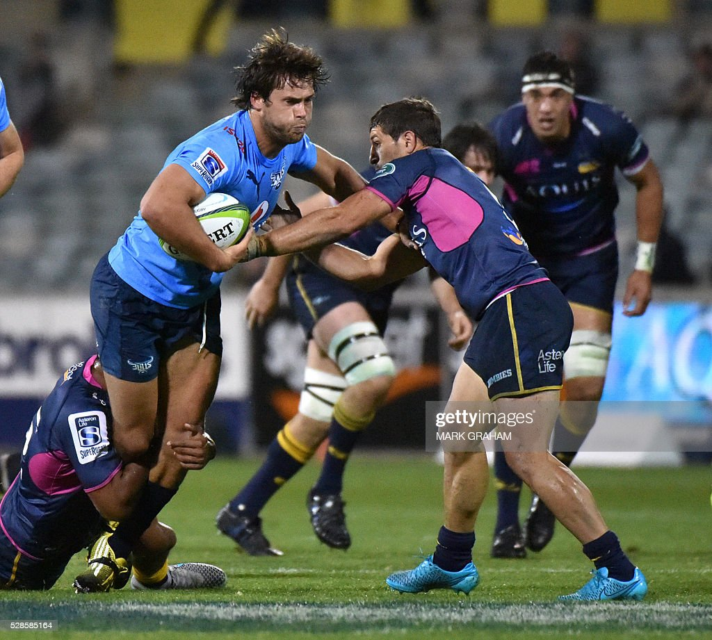 Bulls player Jan Serfontein (C) is stopped by Brumbies players Christian Lealiifano (L) and Tomas Cubelli (R) during the Super Rugby match between the ACT Brumbies and South Africa's Northern Bulls in Canberra on May 6, 2016. / AFP / MARK