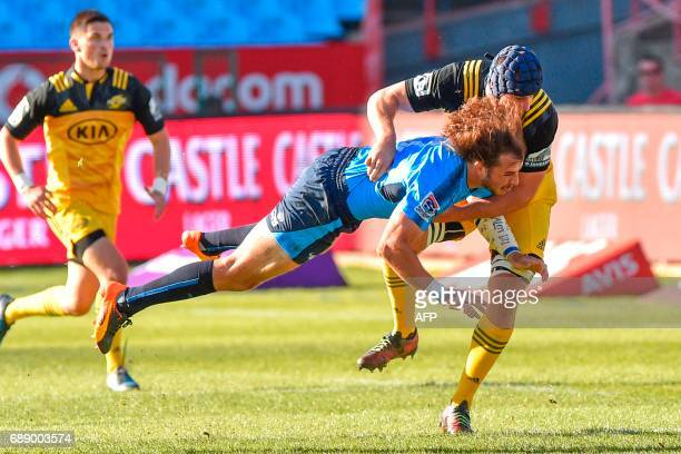 Bulls' South African center Burger Odendaal is tackled by Hurricanes' New Zealander lock Mark Abbott during the SuperXV rugby match between Bulls and...