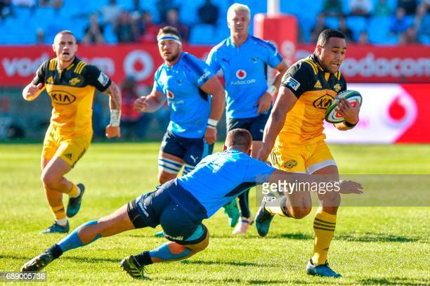 Bulls' South African Duncan Matthews tackles Hurricanes' New Zealander Ngani Laumape as he runs with the ball during the SuperXV rugby match between...