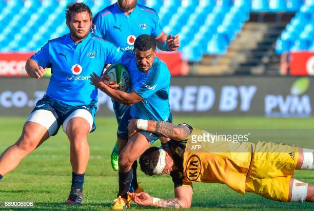 Bulls' South African scrum half Rudy Paige is tackled by Hurricanes' Tongan lock Vaea Fifita during the SuperXV rugby match between Bulls and...