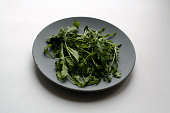 Bunch of arugula salad isolated on gray concrete plate