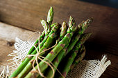 Delicious asparagus fresh on the wooden kitchen table ready to be cooked