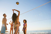 Bunch of attractive friends playing beach volleyball at the beach