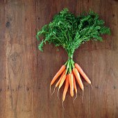 Bunch of baby carrots laying on wooden surface