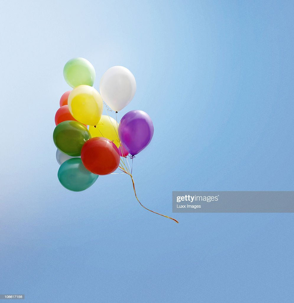bunch of balloons flying in the blue sky stock photo getty images