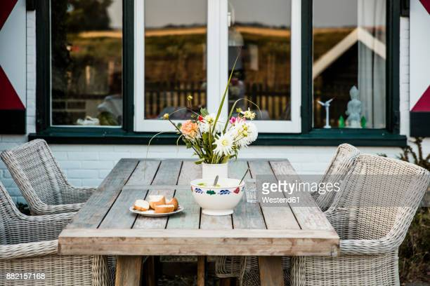 Bunch of flowers and bread on terrace table