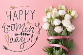 From above Happy Women's day words and bunch of flowers with ribbon on pink background.