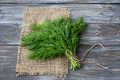 Bunch of fresh dill on a wooden surface. Rustic style, selective focus