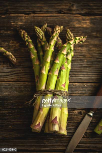 Bunch of fresh green asparagus on a wooden table.