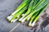 Bunch of fresh green onions on dark or neutral wooden background