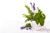bunch of garden fresh herbs in a mortar over white isolated background