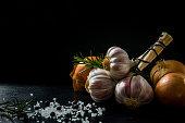 A bunch of garlic, an onion, salt, rosemary and juniper berries.