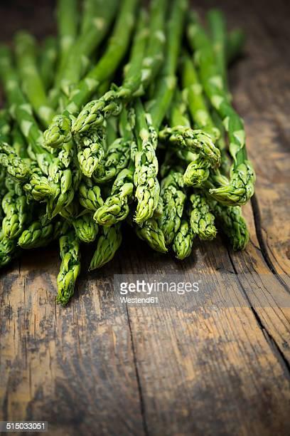 Bunch of green asparagus, Asparagus officinalis, lying on dark wood