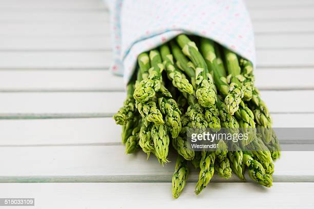 Bunch of green asparagus, Asparagus officinalis, wrapped in cloth lying on white wood