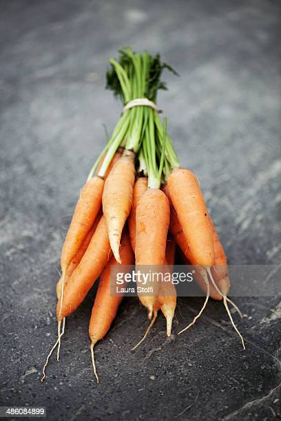 Bunch of organic carrots on ancient stone table