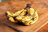 Bunch of overripe bananas on a wooden background