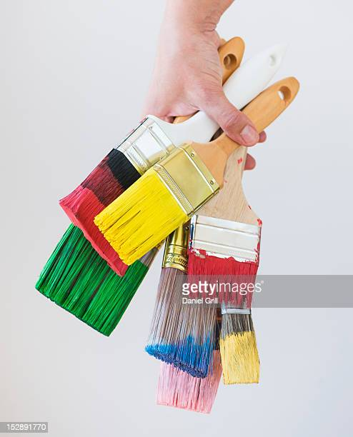 Bunch of paintbrushes held by male hand