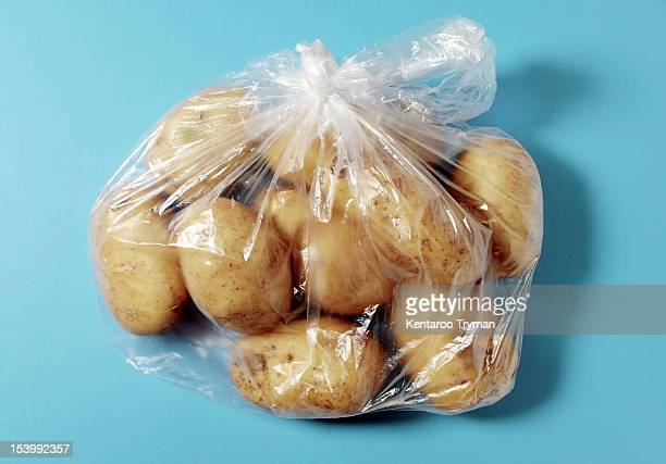 Bunch of potatoes packed in plastic bag over colored background