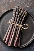 Bunch of fresh purple asparagus in plate on rusty textured background, close up view