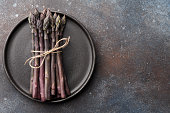 Bunch of fresh purple asparagus in plate on rusty textured background, copy space