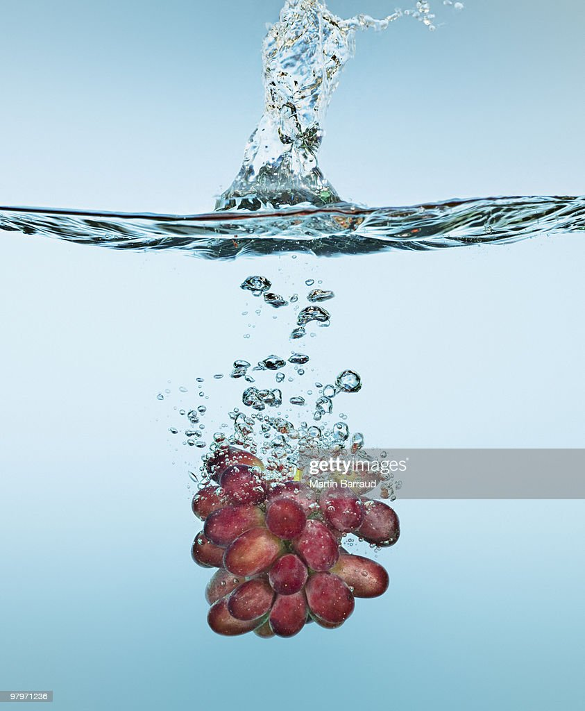 Bunch of red grapes splashing in water : Stock Photo