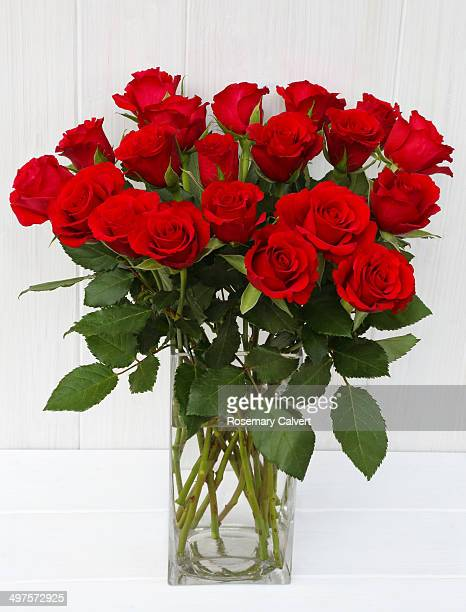 Bunch of red roses in glass vase on white.