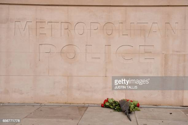 TOPSHOT A bunch of roses is layed at the Metropolitan Police headquarters at New Scotland Yard in central London on March 23 2017 during a minute...