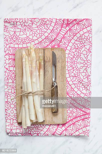 Bunch of white asparagus, chopping board and peeler