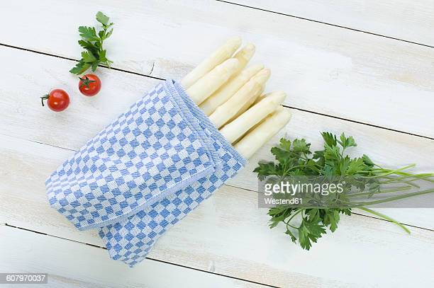 Bunch of white asparagus wrapped in kitchen towel, parsley and cherry tomatoes on wood
