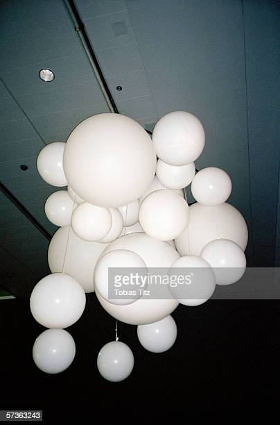 Bunch of white balloons hanging from ceiling