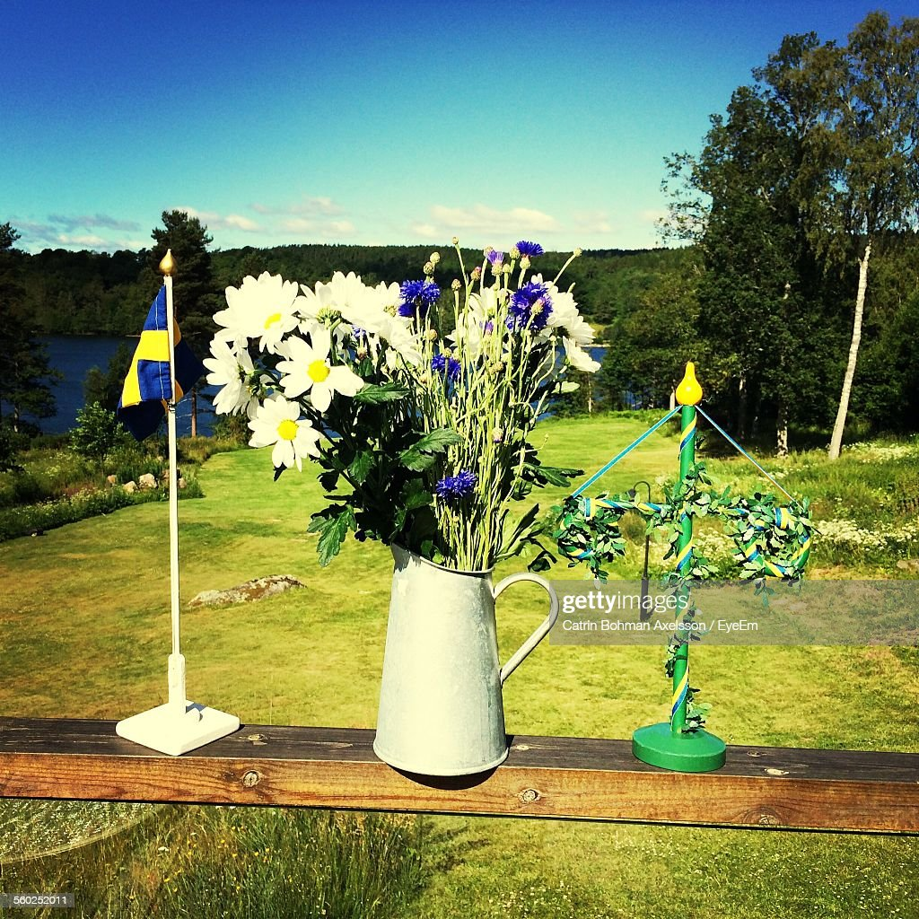 Bunch Of Wildflowers, Knick Knack And Swedish Flag On Wooden Railing