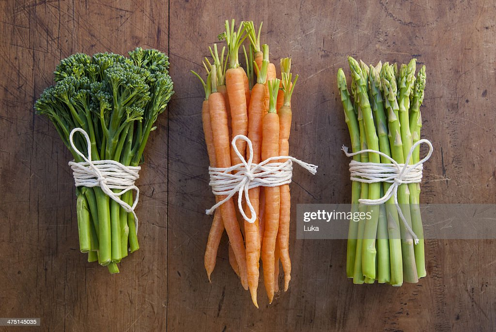 Bunches of carrots, broccoli and asparagus tied with string, still life
