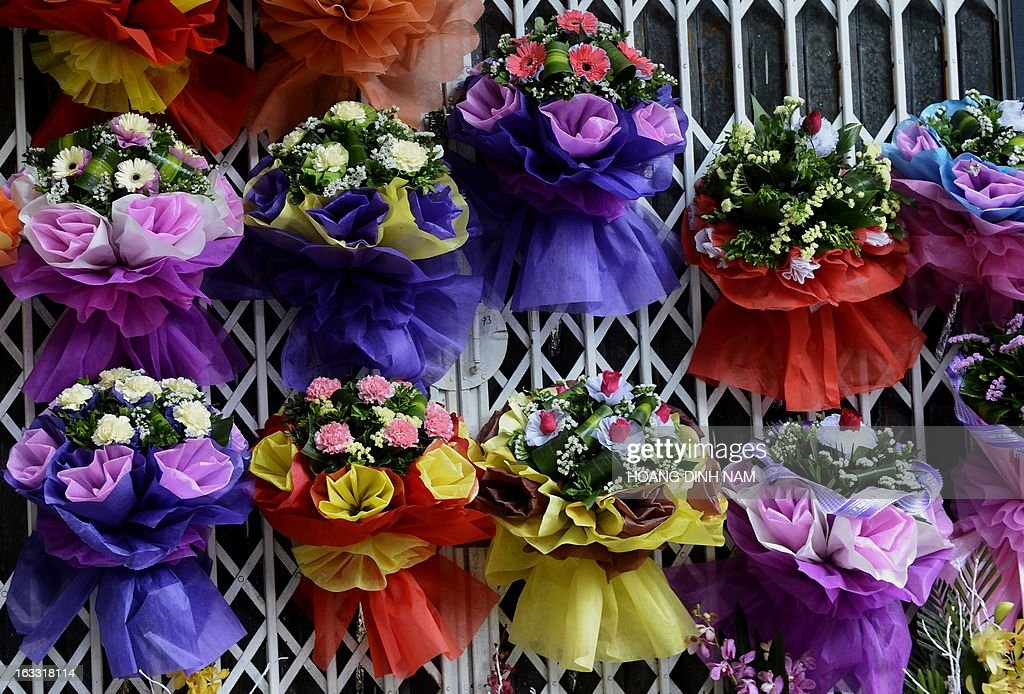 Bunches of flowers are hung up for sale at a florist as Vietnamese celebrate the International Women's Day in Hanoi on March 8, 2013. The day is a good business opportunity for florists with a sharp rise of flowers's prices, especially for roses. AFP PHOTO/HOANG DINH Nam