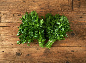 bunches of fresh parsley on a wooden bench