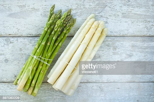Bunches of green and white asparagus on wood