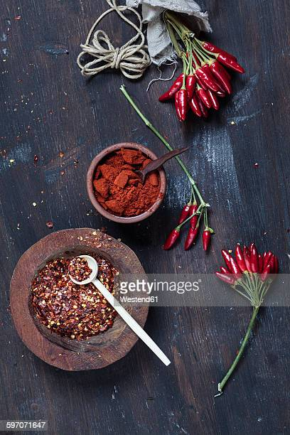 Bunches of red chili peppers, cord plate of chili flakes and bowl with chili powder on wood