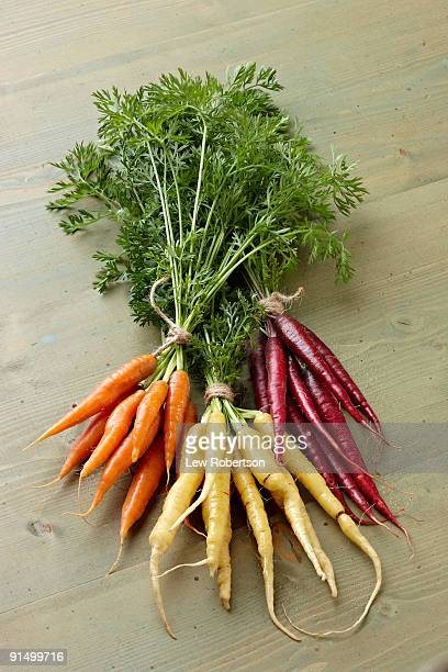 Bunches of yellow, purple and orange carrots