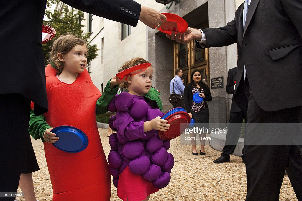Bunch-of-grapes Maden Murray, 4, and her sister, carrot Davan Murray - who just turned 6 - pass out plates, with a message attached urging timely passage of a school nutrition bill, to Senate staffers arriving for work at the Dirksen Senate Office Building. The Center for Science in the Public Interest organized the push to get the 'Healthy, Hunger-Free Kids Act' (S. 3307) to the Senate floor this month. The message glued to each plate, which were red and blue respectively, was headlined, 'Congress has a lot on its plate, but it needs to address what's on kids' plates - now!'