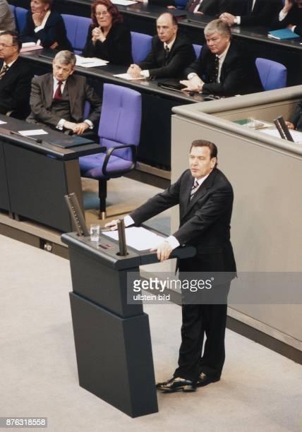 Bundeskanzler Gerhard Schröder spricht das erste Mal am Rednerpult des Plenarsaales im neu gestalteten Reichstag in Berlin Hinter ihm ist die...