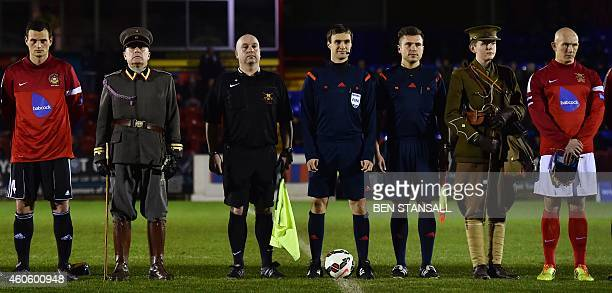 Bundeswehr football captain Alexander Hess Swiss referee Stephan Klossner and British Army football captain Keith Emmerson stand on the pitch...