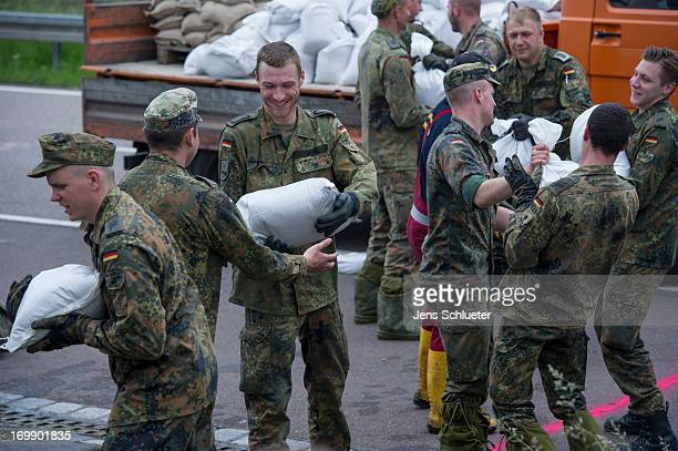 Bundeswehr soldiers stack sandbags to strengthen a dam on the outskirts of the city against the rising Saale river on June 4 2013 in Halle Germany...