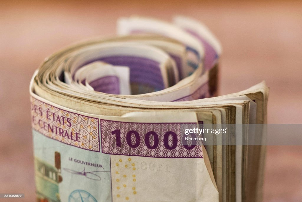 A bundle of 10,000 denomination Central African franc banknotes sit in this arranged photograph in N'Djamena, Chad, on Wednesday, Aug. 16, 2017. African Development Bank and nations signed agreement to finance a project linking the town of Ngouandere in Cameroon and Chads capital, NDjamena, according to statement handed to reporters in Cameroonian capital, Yaounde in July. Photographer: Xaume Olleros/Bloomberg via Getty Images